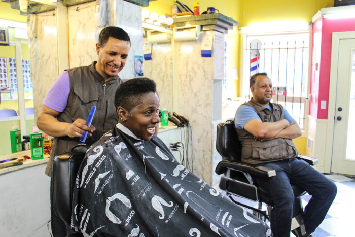 Barber Daniel Abaynhe (right) finishes up Tracey D. Watkin's hair at Update barber shop on 23rd, as barber Adal Shimelis chats with them. (Photo by Venice Buhain.)