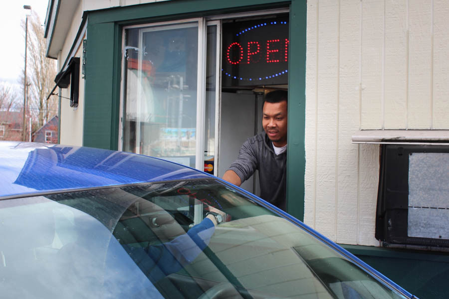 Abodolloh Zay serves a drink to a drive-through customer at First Cup Coffee. Fewer cars have come through during the months of construction. (Photo by Venice Buhain.)
