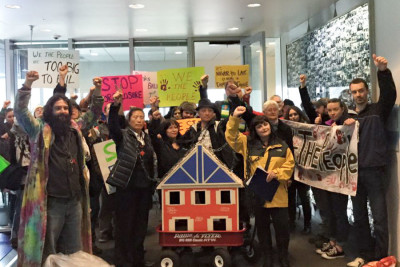 Activists from SAFE and Valley & Mountain join Belgrano in chaining themselves to a model house that they carried to City Hall, the King County Recorder's Office and JP Morgan Chase offices.(Courtesy photo)