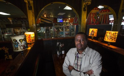 Berhane Amanuel, owner of East Africa Imports (and restaurant) stands inside his Seattle restaurant. His store can be seen through the arches at top. East Africa Imports is a tiny little story and eatery in The Promenade, a shopping center in the Central District. It was opened in 2002 by Amanuel and his Central District native wife and they put 100k+ into adding a restaurant about 5/6 yrs ago. They recently found out that Vulcan plans to demolish/develop the shopping center meaning they'll have to move and may not be able to afford to open a restaurant again.