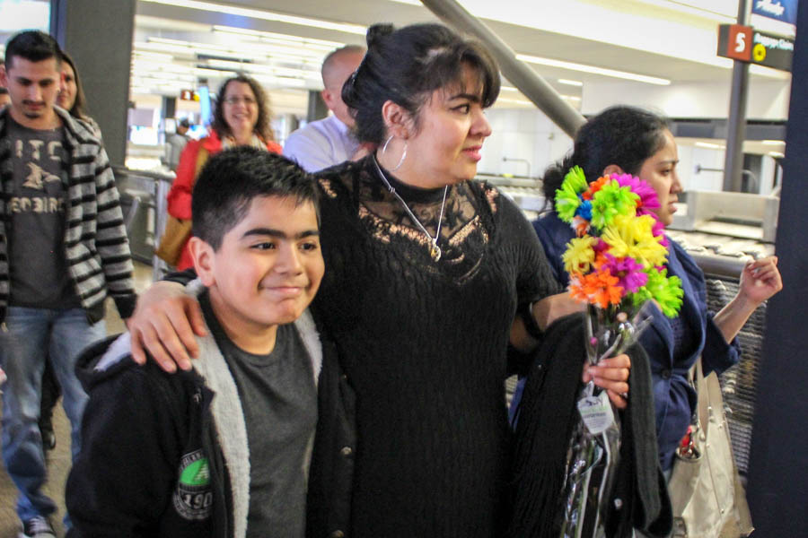 Nestora Salgado (center) puts her arm around her grandson Cristian, at Seattle-Tacoma International Airport as she returns from Mexico after kidnapping charges against her were dropped. (Photo by Venice Buhain).