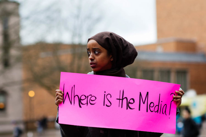 "Vigil organizer Nafiso Egal, sophomore, holds a sign that reads, ""Where is the media?"" UW Students call for attention to the lives and deaths of the black Muslims. (Photo by Raisa Janjua)"