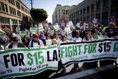 Fast-food workers in Los Angeles marched for a $15 minimum wage last November. A plan to phase in California's minimum wage to $15 by 2022 is moving through the legislature. (Photo from REUTERS / Lucy Nicholson)