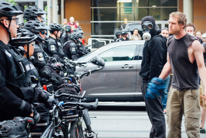 "A protestor confronts cops on May Day 2015. (Photo from Flickr by <a href=""https://www.flickr.com/photos/adamcohn/"">Adam Cohn</a>)"