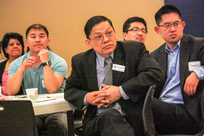 Mohan Gurung of the Washington Commission on Asian Pacific American Affairs (center) and other attendees listen at a recent forum on Washington state legislative bills affecting people in the Asian American community. (Photo by John Stang.)