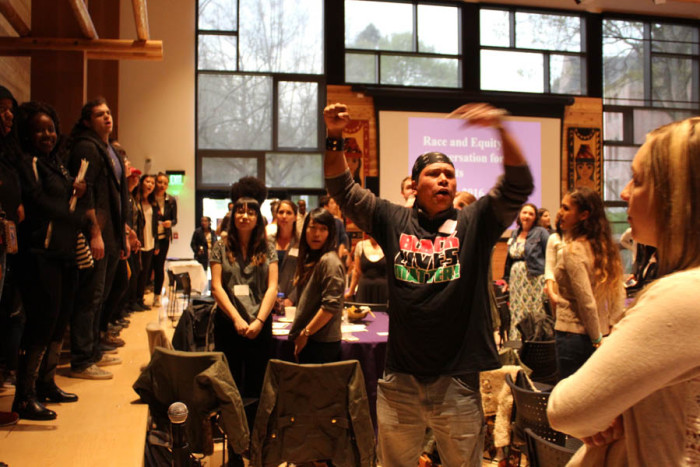 """University of Washington student Michael """"Renaissance"""" Moynihan leads a chant as a Black Lives Matter demonstration disrupts a UW Race and Equity Initiative event at Intellectual House on Tuesday. Recent incidents involving students of African descent and UW police have increased tensions. (Photo by Venice Buhain)"""