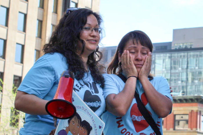 Maricela Osorio (right) wipes her eyes after getting emotional addressing a crowd at a rally supporting Obama's immigration actions in front of the federal building in downtown Seattle, while Casa Latina organizer Cariño Barragán (left) comforts her. (Photo by Venice Buhain.)