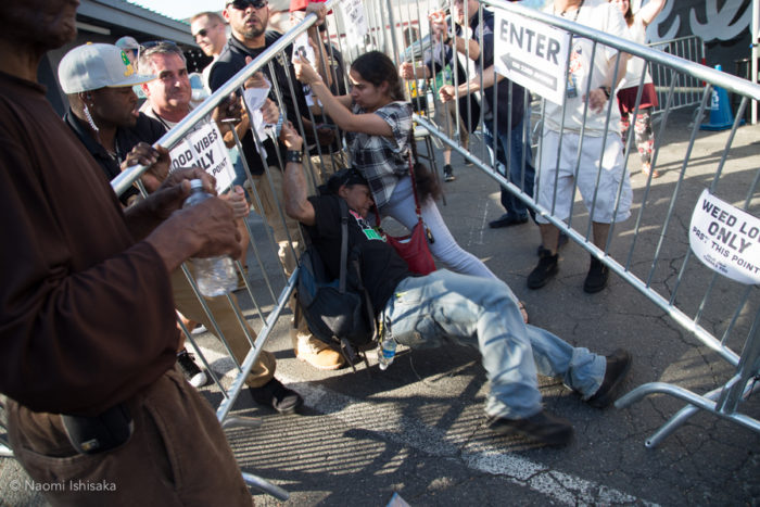 Activist Michael Renaissance Moynihan, middle left, struggles to avoid being crushed by party fence after shop staff try to push it back towards Uncle Ike's. Owner Ian Eisenberg is third from the left. (Photo by Naomi Ishisaka)