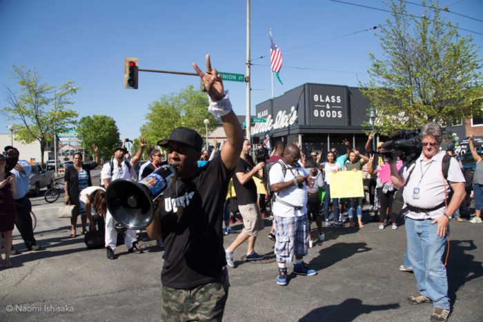 Artist and event organizer Draze leads protesters outside of Uncle Ike's. (Photo by Naomi Ishisaka)
