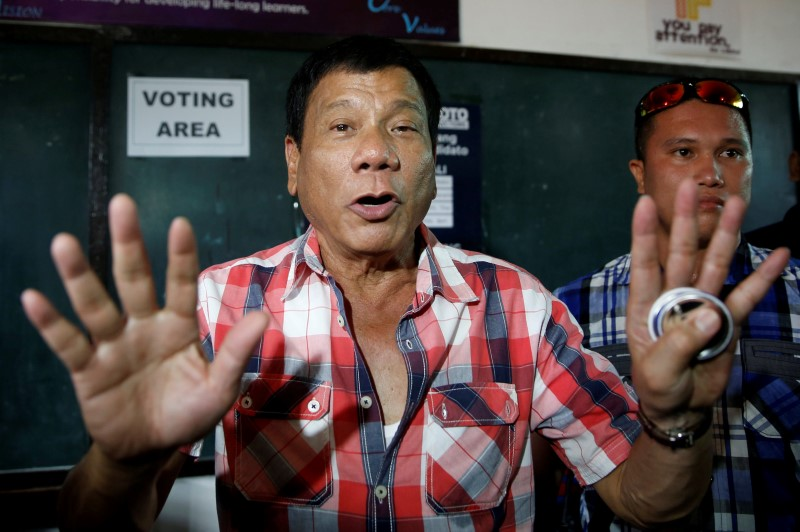 "Presidential candidate Rodrigo ""Digong"" Duterte talks to the media before casting his vote at a polling precinct for national elections at Daniel Aguinaldo National High School in Davao city in southern Philippines, May 9, 2016. (Photo by Erik De Castro for Reuters.)"