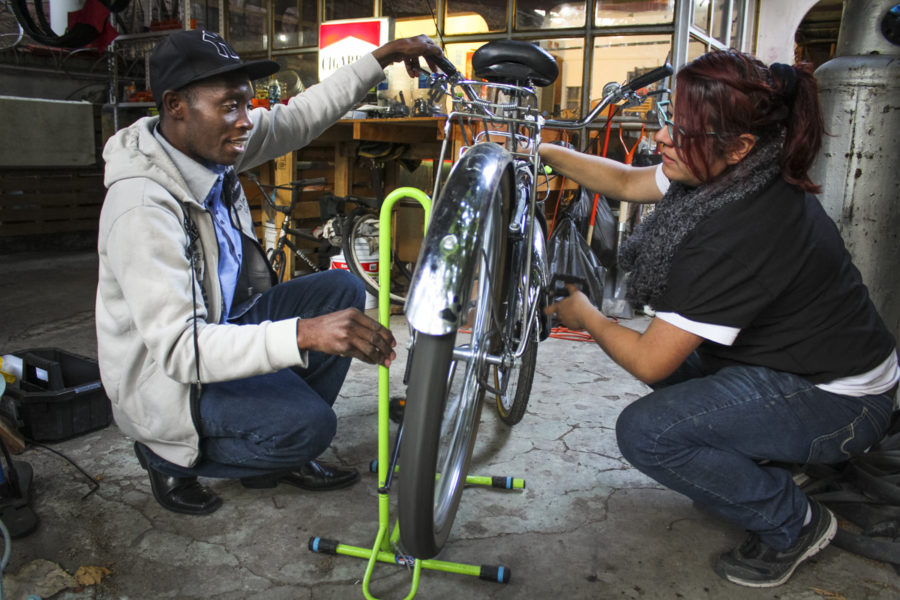 Viljean Celian (left), 33, repairs bicycles at Quiquica, a workshop that trains and employs migrants, refugees and asylum applicants in Mexico City. He is seen here with Luz Abril Reza López, the coordinator of Quiquica. (Photo by Mayela Sánchez, GPJ Mexico, for Global Press News Service.)