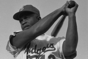 Jackie Robinson posing in his Dodgers uniform in 1954. (Photo by Bob Sandberg and reprinted under a Creative Commons License)