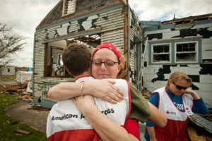 Tonya Miller hugs a Red Cross volunteer in front of her home in Joplin, Missouri following the 2011 tornado. (Photo from Flickr by Ozarks Red Cross)