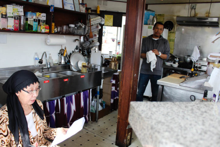 Nop Zay, left, examines paperwork at her coffee kiosk on 23rd Avenue as her son, Abodolloh Zay (right) works in the kitchen. (Photo by Venice Buhain.)
