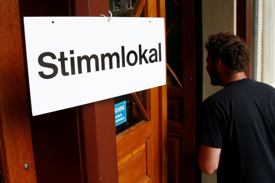 """People arrive in a ballot office to vote on whether to give every adult citizen a basic guaranteed monthly income of 2,500 Swiss francs ($2,560), in a school in Bern, Switzerland, June 5, 2016. The sign reads, """"Ballot office.""""    (Ruben Sprich for Reuters.)"""