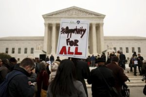 A demonstrator holds a sign aloft as the affirmative action in university admissions case was being heard at the Supreme Court in Washington, December 9, 2015. (Photo by Kevin Lamarque for Reuters.)