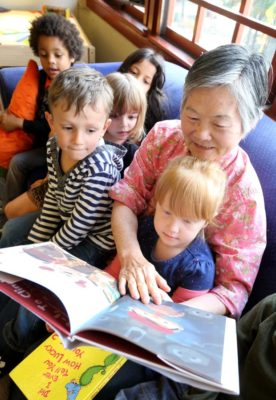 """Fen Fang Jiang, 72, reads to kids at Pike Market Childcare in the Pike Place Market. Jiang is part of the """"Foster Grandparent"""" program. (Photo by Greg Gilbert / The Seattle Times)"""