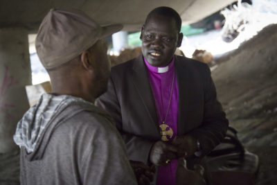 "Rev. Bishop David Kuol of the Awerial Diocese of South Sudan talks with a resident of The Jungle underneath I-5. The Reverend is touring the United States and visiting with Sudanese who have resettled here, including several ""Lost Boys"" now living in the homeless encampment. (Photo by Sy Beam / The Seattle Times)"