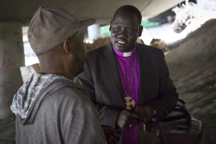 "Rev. Bishop David Kuol of the Awerial Diocese of South Sudan talks with a resident of The Jungle underneath I-5. The Reverend is touring the United States and visiting with Sudanese who have resettled here, including several ""Lost Boys"" now living in the homeless encampment. (Photo by Sy Bean / The Seattle Times)"