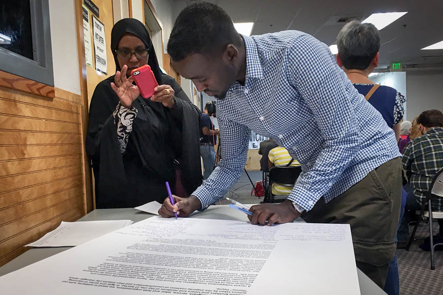 Amina Ahmed, of SeaTac, takes a photograph of Awdoon Mohamed, as he signs a letter to Attorney General Bob Ferguson urging his office to investigate the city of SeaTac. (Photo by Venice Buhain)