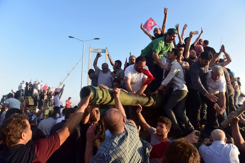 Supporters of Tukish President Tayyip Erdogan celebrate after soldiers involved in the coup surrendered on the Bosphorus Bridge in Istanbul, Turkey July 16, 2016. (Photo by Yagiz Karahan for Reuters)