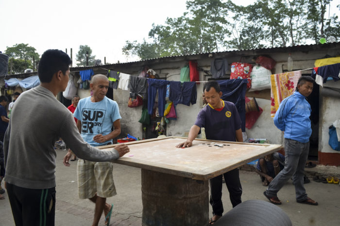 Shanta Lama, in dark blue shirt with yellow emblem, plays carrom, a board game in the courtyard at Kavre District Prison. (Photo by Kalpana Khanal for GPJ Nepal)