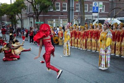 Members of the Seattle Chinese Community Drill team look on as Aziza Alabe launches into a cartwheel.