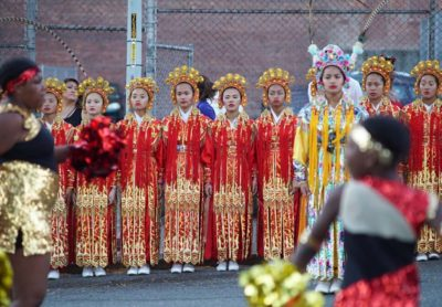 Seattle Chinese Community Girls Drill Team stand at attention while the Electronettes perform at the Chinatown Seafair Parade.
