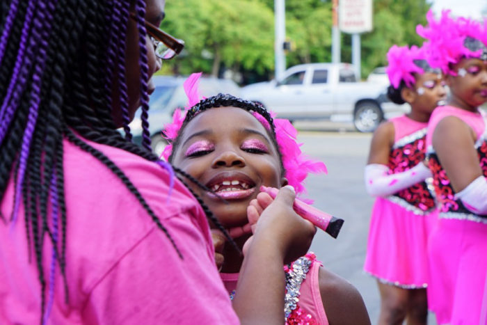 Elegance Drill Team Coach Veronica Warren applies make-up to her daughter Jade Marie Warren's lips before the Jubilee Parade in White Center.