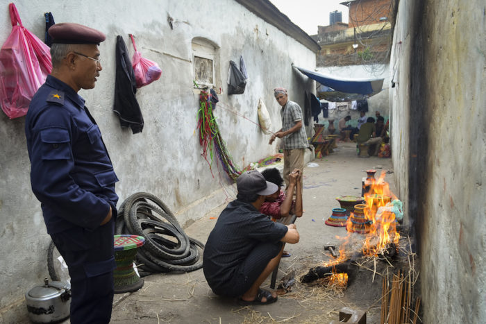 Purna Bahadur Pradhan, 46, the police officer in charge of security at the prison, watches two prisoners cook. The officer visits the prison twice a day to monitor activities there. (Photo by Kalpana Khanal for GPJ Nepal)