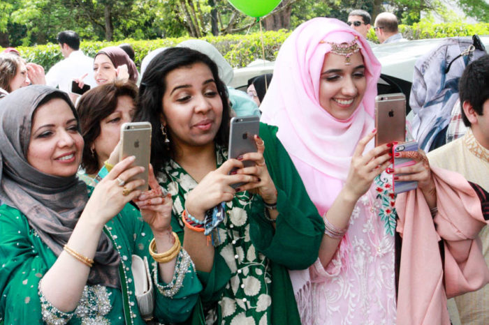 Mosque members get ready to celebrate Eid by taking selfies outside the Muslim Association of Puget Sound's masjid in Redmond. (Photo by John Stang.)