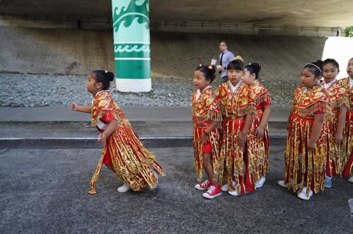 Smaller members of the Chinese Community Drill Team run to catch up.