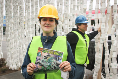 """Stand.earth Seattle coordinator Sierra Klingele holds a copy of """"Super Mermaid"""" a satirical comic book distributed by Stand at Emerald City ComicCon as part of the campaign. (Photo by Esmy Jimenez)"""