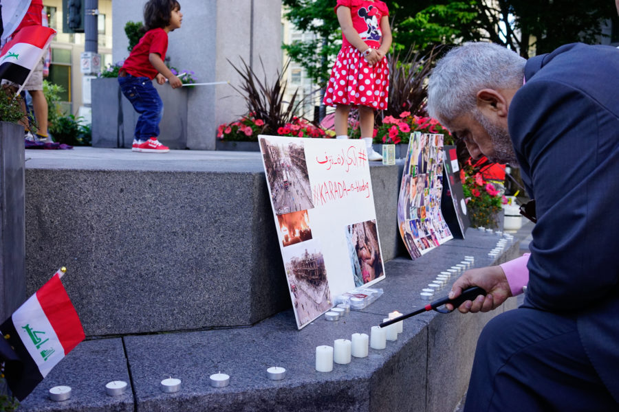 A man lights a candle at a vigil for Iraq at Westlake Park Wednesday night. (Photo by Chloe Collyer)