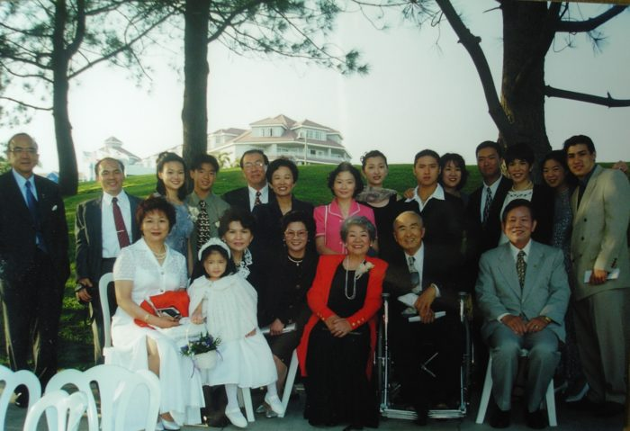 The author sits in her mother's lap at a family wedding in 1999, surrounded by her immediate and extended family