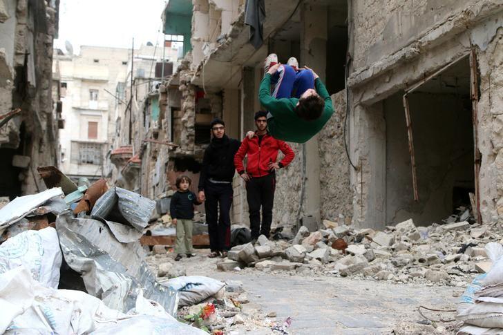 Gymnast Ahmad al-Sawas performs gymnastic moves near damaged buildings in the rebel-held Bustan al-Qasr neighbourhood of Aleppo, Syria March 26, 2016. (Photo by Abdalrhman Ismail for Reuters.)