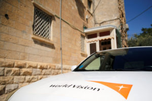 The logo of U.S.-based Christian charity World Vision is seen on a car parked outside their offices in Jerusalem August 4, 2016. (Photo by Ammar Awad for Reuters.)