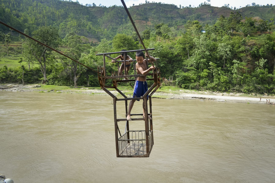 Children enjoy a risky ride in a tuin, a rope and pulley system, over the Trishuli River in Nepal's Dhading district. The government plans to replace all 155 of Nepal's tuins with suspension bridges. (Photo by Kalpana Khanal, GPJ Nepal)