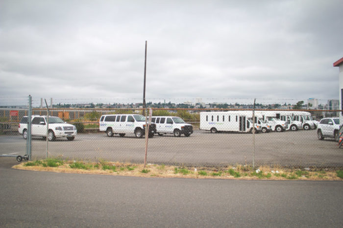 Vans and busses used to transport detainees and detention center staff are parked across from the NWDC. The facility is owned and operated by a private corporation called The GEO Group. (Photo by Damme Getachew)