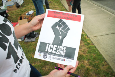 Immigration reform activist Maru Mora Villalpando holds a flier outside the NWDC. (Photo by Damme Getachew)