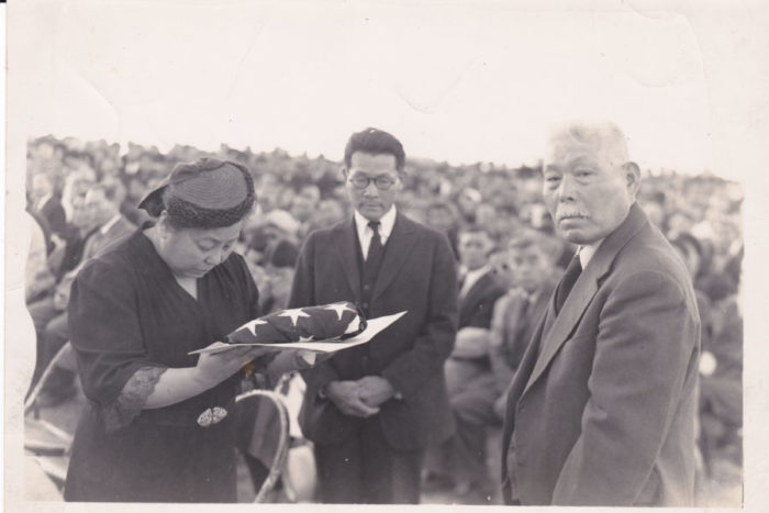"Tom Ikeda's grandparents Fred Suyekichi and Akino Kinoshita (left and center) receive a flag in honor of their son Staff Sergeant Francis ""Bako"" Kinoshita, killed in action in World War II, accompanied by a family friend. (Photo courtesy Tom Ikeda.)"