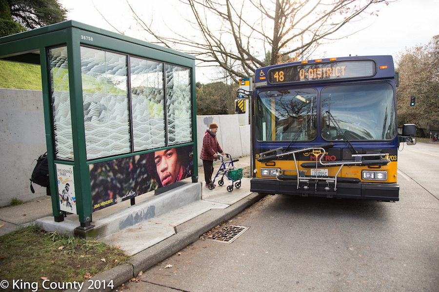 A passenger boards a King Country Metro bus in 2014, at a stop adorned with an image of Jimi Hendrix. (Photo by King County via Flickr.)