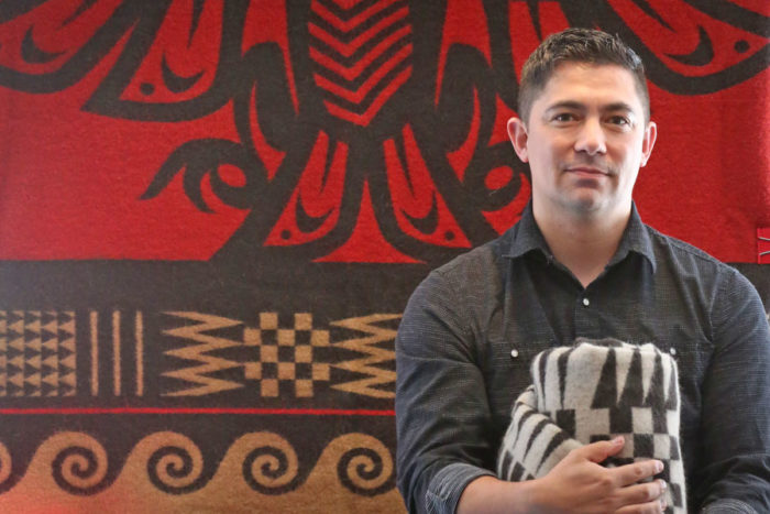 """Native artist Louie Gong with blankets he designed and will sell at his new store,""""Eighth Generation""""opening Saturday in the Pike Place Market. (Photo by Greg Gilbert / The Seattle Times)"""