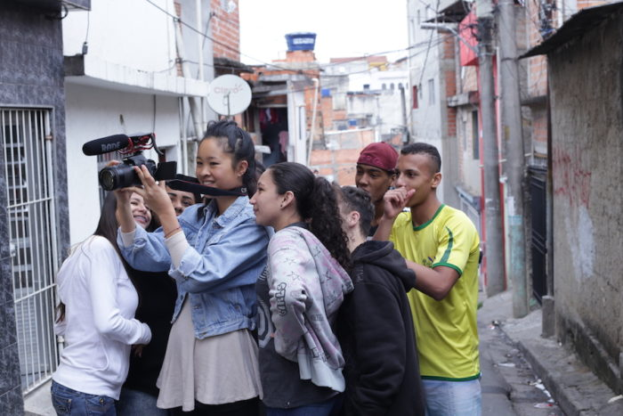 Author filming a funk rap in the streets of the Heliópolis favela during a youth media workshop. Credit: Thiago Nascimento