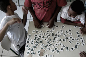 Children play word dominoes in an afterschool program in the Heliópolis favela in São Paulo. (Photo by Bruno Ruiz)