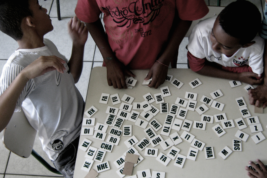 Children play word dominoes in an afterschool program in the Heliópolis favela in São Paulo. (Photo by Bruno Ruiz)