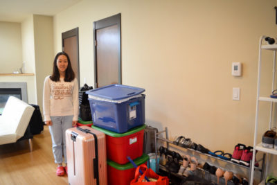 Sylvia Zhao stands by her unpacked boxes in the living room of the new townhouse she just moved into. (Photo by Katherine Jinyi Li)