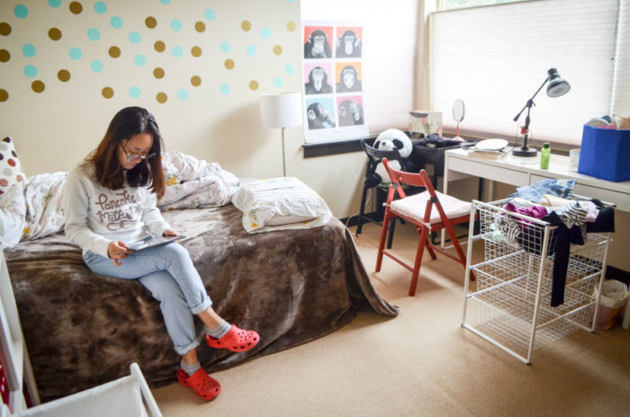Sylvia Zhao, 22, sits in her newly rented room in a townhouse owned by a fellow Chinese international student in Lake City. Zhao graduated from UW last year and hopes to find a job and stay in Seattle. (Photo by Katherine Jinyi Li)