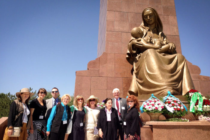 "The 2013 Seattle Sister Cities Delegation, under the ""Happy Mother"" statue in Tashkent. (Courtesy photo)"