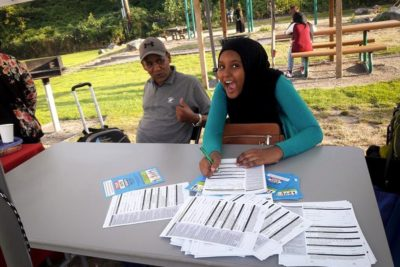 A student volunteer helps people register to vote in advance of the September voting workshop at Somali Community Services of Seattle. (Photo courtesy of Sahra Farah)